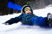 Boy sledding at Pinehurst Park