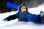 Boy sledding at Pinehurst Park